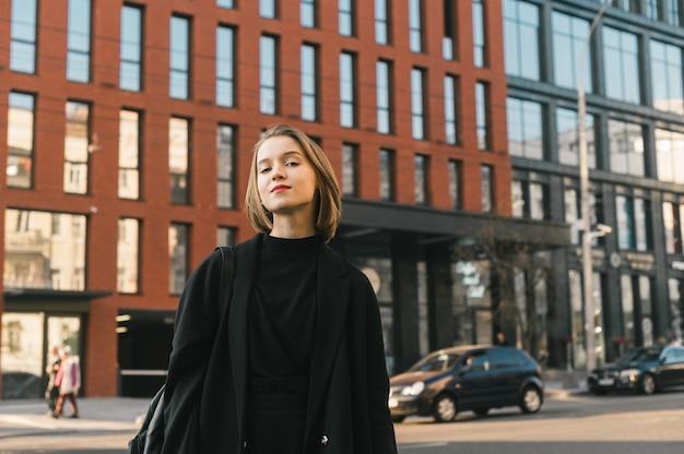 カジュアルなファッションの魅力的な女の子は、近代建築と通りを背景にポーズをとる