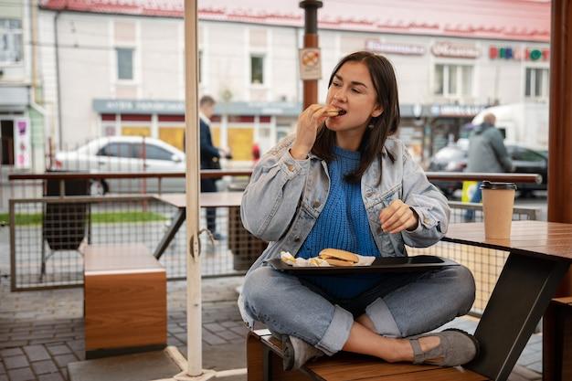 カジュアルなスタイルの魅力的な女の子が、カフェのサマーテラスに座ってコーヒーを飲みながらハンバーガーを食べる。