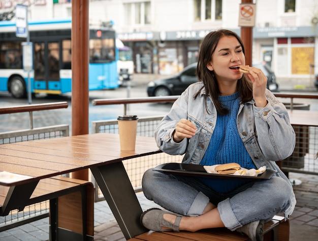 캐주얼 스타일의 매력적인 소녀는 카페의 여름 테라스에 앉아 커피와 함께 햄버거를 먹는다