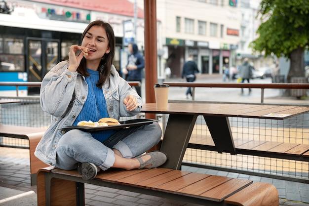 カジュアルなスタイルの魅力的な女の子は、カフェの夏のテラスに座ってコーヒーとハンバーガーを食べる