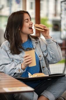 캐주얼 스타일의 매력적인 소녀는 여름 테라스에 앉아 커피와 함께 햄버거를 먹는다