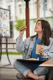カジュアルなスタイルの魅力的な女の子は、夏のテラスに座ってコーヒーとハンバーガーを食べる