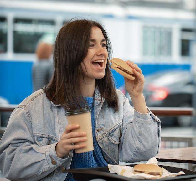 カジュアル スタイルの魅力的な女の子は、夏のテラスに座ってファーストフードを楽しんでいます。