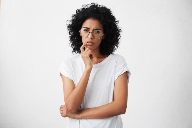 カジュアルなtシャツと丸いメガネの目を絞って、あごに手を保つ魅力的な女の子
