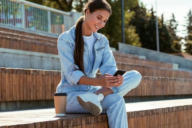 デニムの服を着た魅力的な女の子が公園のベンチに座ってメッセージを書いています。美しいブルネットの女性