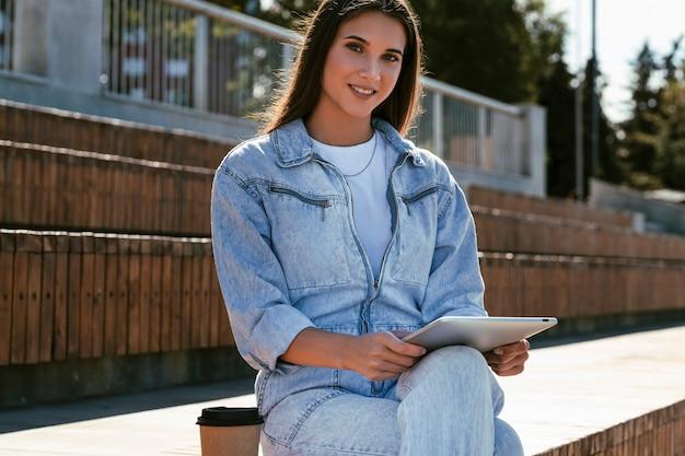 デニムの服を着た魅力的な女の子が公園のベンチに座って、スマートタブレットを手に持っています。美しい女性の肖像画