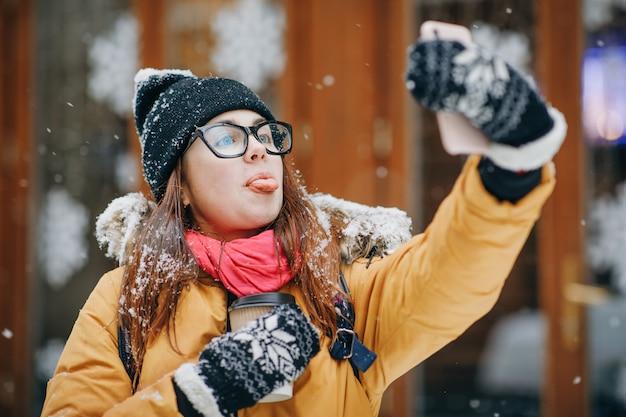안경에 매력적인 여자는 그녀의 스마트 폰에 selfie를 만든다. 여자는 휴대 전화에 사진을 만든다. 어디에나있을 수 있습니다.