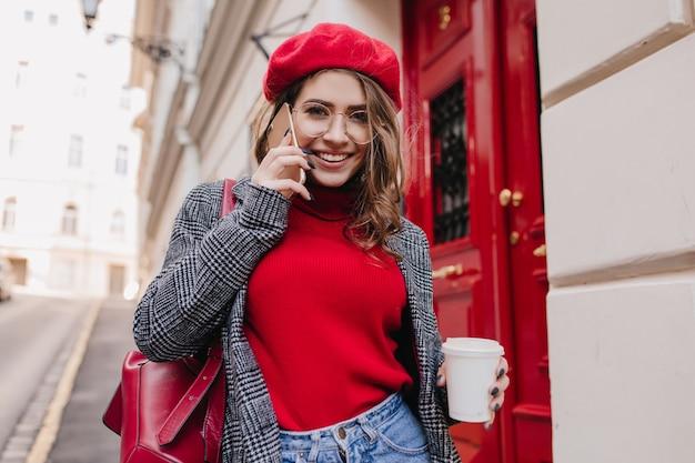 街で週末を過ごし、コーヒーを楽しんでいる機嫌の良い魅力的な女の子