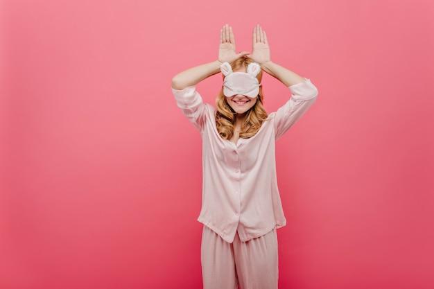 ピンクの壁にふざけてポーズをとるナイトスーツの魅力的な女の子。寝る前にパジャマを着て笑っているヨーロッパの女性の屋内写真。
