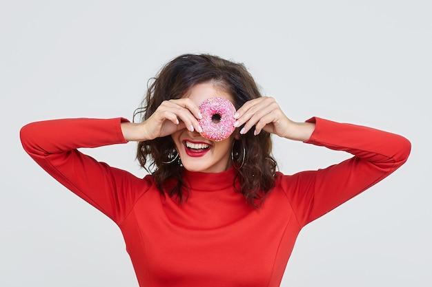 Привлекательная девушка в красном платье смотрит через пончик