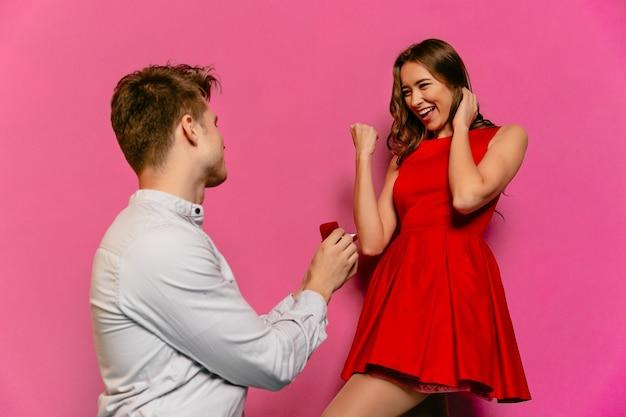Привлекательная девушка в красном платье, показывающая знак победы после предложения о браке