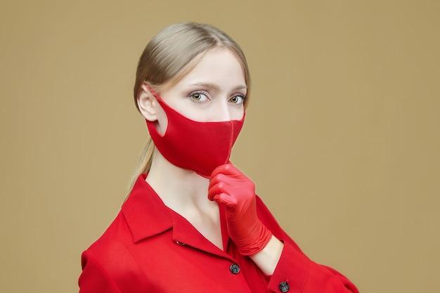 赤い手袋とマスクの魅力的な女の子。 covid19コロナウイルスの予防の概念。黄色の背景のスタジオでのフォトセッション