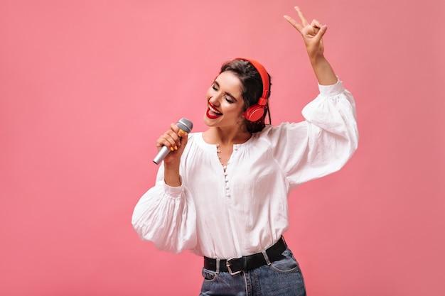 Привлекательная девушка в красных наушниках поет в микрофон на розовом фоне. красивая дама с темными волосами в белой стильной блузке слушает музыку.