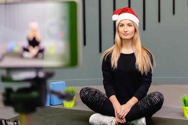 Привлекательная девушка в шляпе санты делает фитнес-упражнения и снимает себя на камеру.