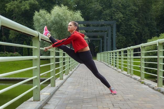 スポーツウェアの魅力的な女の子は、都市公園の橋でウォームアップを行います。