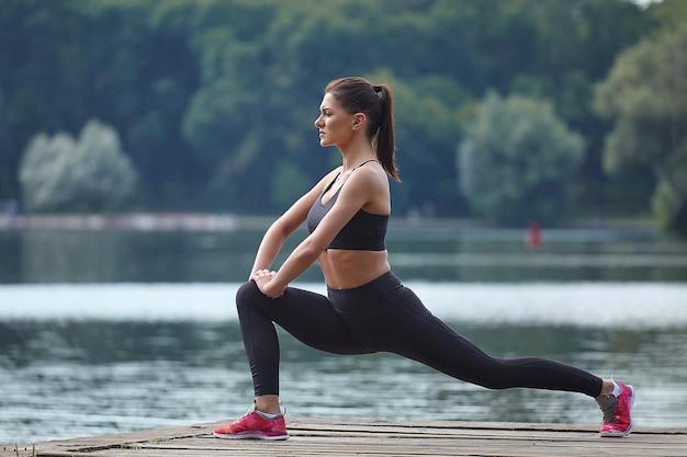 Привлекательная девушка в спортивной одежде делает гимнастические упражнения на деревянном пирсе в городском парке.