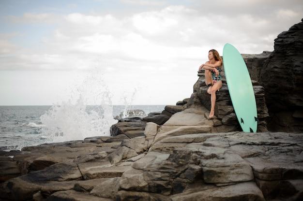 대서양과 맑은 하늘 위에 바위에 서핑 보드 근처에 앉아 멀티 컬러 수영복에 매력적인 여자