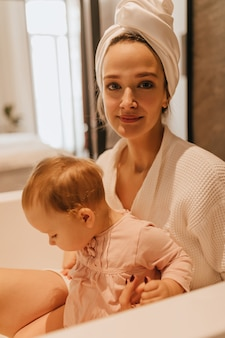Привлекательная девушка в полотенце на голове и в халате смотрит в камеру и обнимает свою дочь, сидя в ванной.