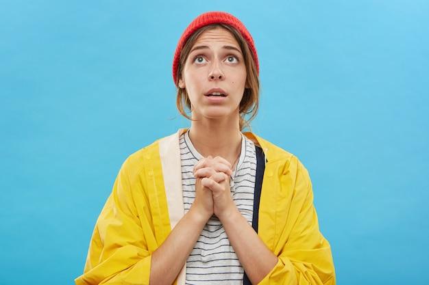 Привлекательная девушка в модной одежде смотрит вверх глазами, полными надежды и доверия, со сложенными руками, когда она молится богу, прося о помощи. красивая религиозная молодая женщина молится