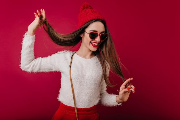 Привлекательная девушка в модной красной шляпе играет со своими каштановыми волосами, позируя на бордовом пространстве