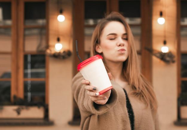 建物の立っている背景に暖かい服で魅力的な女の子は紙コップを保持しています。
