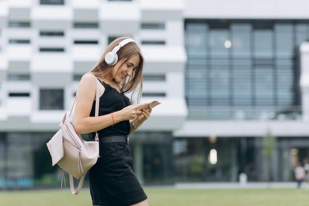魅力的な女の子は、都市の通りを歩きながら、ヘッドフォンで携帯電話から音楽を聞いて、メッセージを入力しています。ライフスタイル。