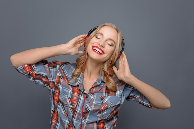 Attractive girl is listening to music through headphones