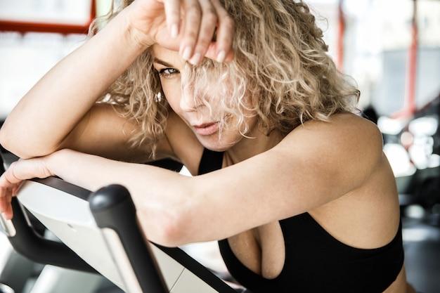 魅力的な女の子がエアロバイクのクローズアップに横たわっています。