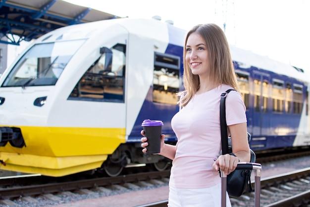 Привлекательная девушка стоит с багажом на вокзале и ждет поезда, портрет студента на поезде, копия пространства