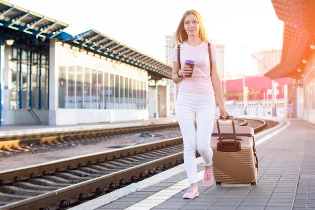Привлекательная девушка стоит с багажом на вокзале и ждет поезда, студент едет в путешествие, она идет по перрону, копирует пространство