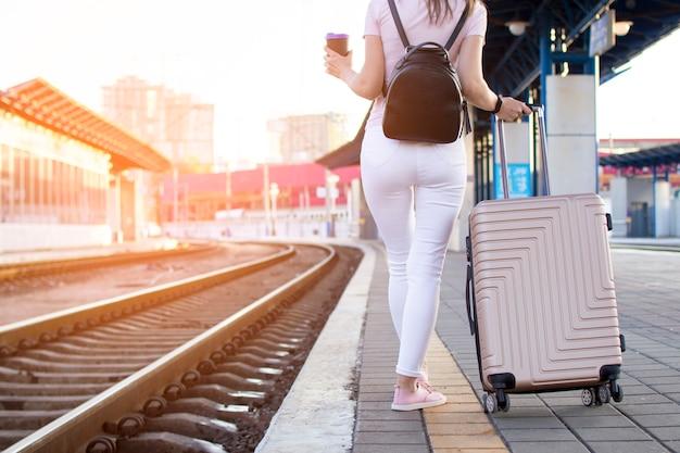 Привлекательная девушка стоит с багажом на вокзале и ждет поезда, студент отправляется в путешествие, она идет по перрону с кофе, копирует пространство