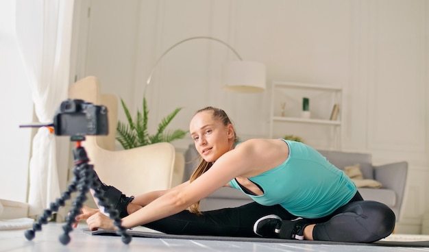 An attractive girl is vlogging about online fitness, she is filming a vlogging doing stretching exercises on a rug in a bright room. a young girl is doing distance learning online while blogging.