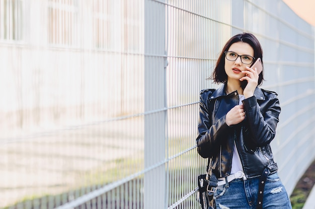 Attractive girl in leather jacket in glasses talking on phone