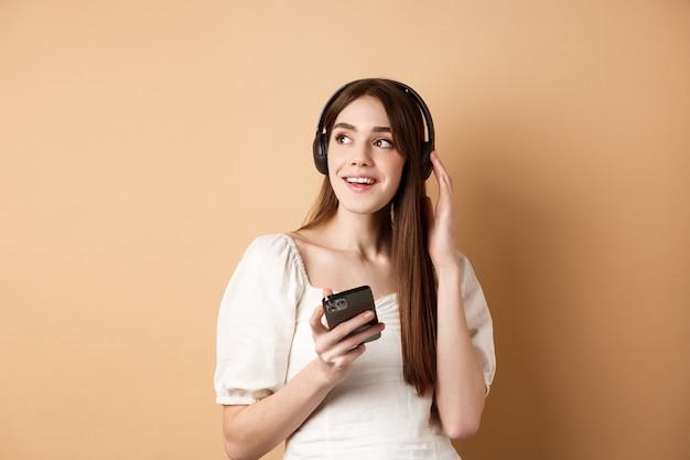 Привлекательная девушка слушает музыку в беспроводных наушниках, держит мобильный телефон и смотрит в сторону с мечтательной улыбкой, бежевом фоне.