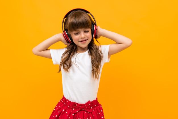 Привлекательная девушка слушает музыку на желтом фоне студии.