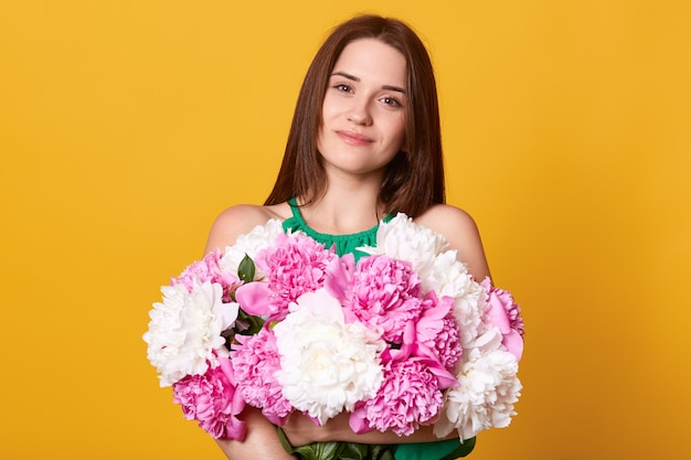 Attractive girl looking at camera with pleased facial expression, holding huge bouquet of flowers