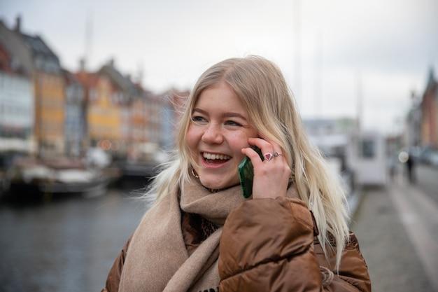 魅力的な女の子が友達と電話をかけ、好きなニュースを受け取って幸せそうに笑う