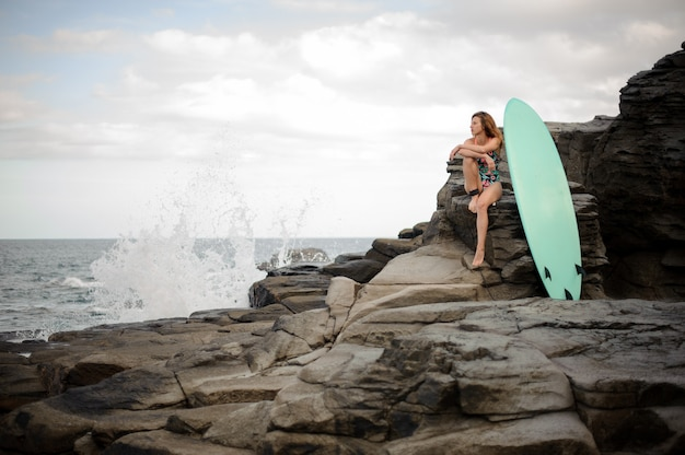 Attractive girl in the multi colored swimsuit sitting near the surfboard on the rock over the atlantic ocean and clear sky