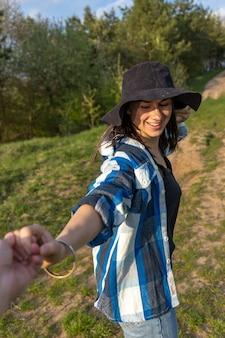 カジュアルなスタイルで春の森を散歩する魅力的な女の子