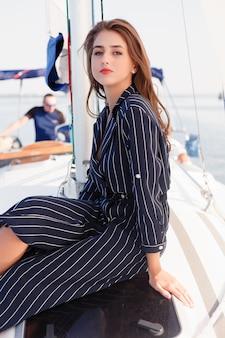 Привлекательная девушка на яхте в летний день. закройте модный портрет потрясающей романтической женщины, позирующей яхту. носить нарядное платье, летний наряд. голубое небо. закат