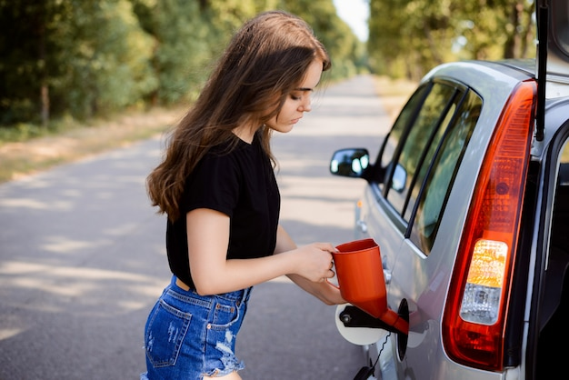 Attractive girl opens the lid of the fuel tank in the car and puts red bailer inside to fuel the tank. concept of filling fuel tank in the trip