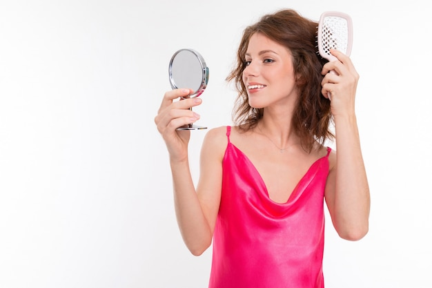 Attractive girl in a pink dress combs her hair while looking in the mirror