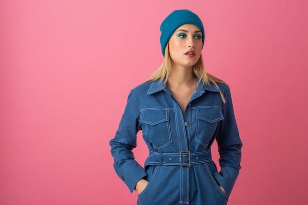 Привлекательная девушка позирует на розовом фоне в общей модной тенденции джинсовой ткани