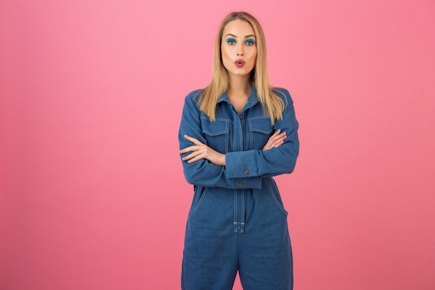 Attractive girl posing on pink background in denim overall fashion trend