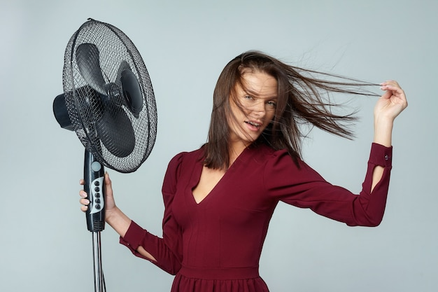 Привлекательная девушка позирует с веером в студии