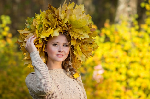 Attractive girl posing with a wreath of leaves.