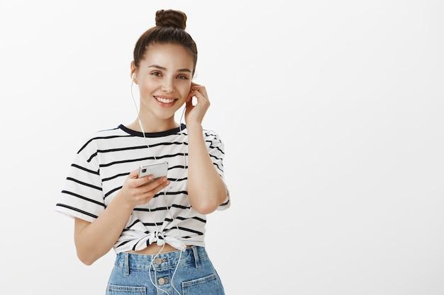 Attraente ragazza indossa le cuffie per ascoltare musica o podcast online, tenendo lo smartphone