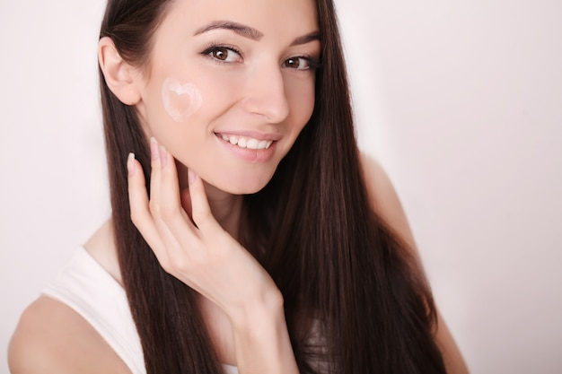 Attractive girl putting anti-aging cream on her face