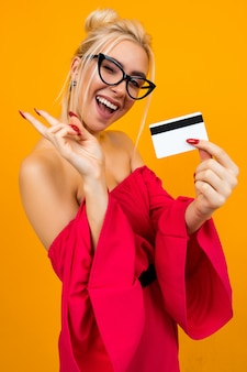 Attractive girl in a red dress holds a credit card with a layout for the bank on a yellow surface