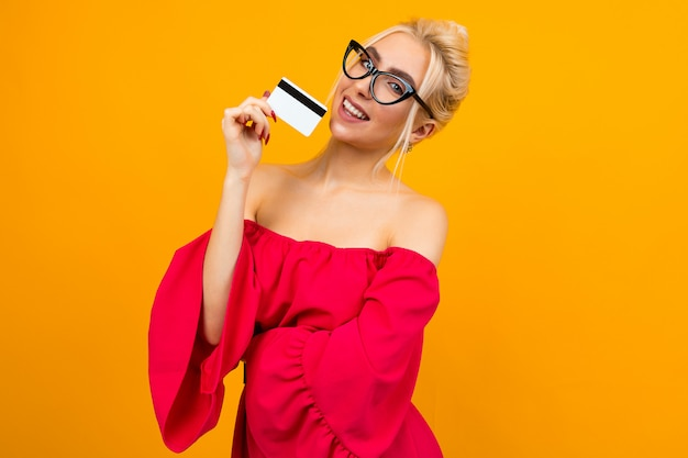Attractive girl in a red dress holds a credit card